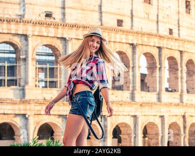 Beautiful young blonde woman with blue at colosseum smiling. Large hat and squared shirt. Rome, Italy - Stock Photo