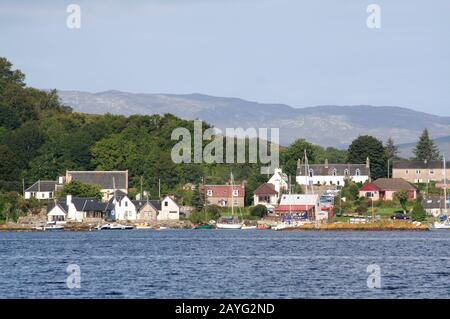 Tayvallich village and boats in the harbour from the water, Loch Sween, Argyll, Scotland - Stock Photo