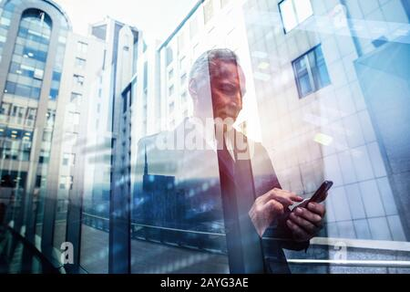 Senior businessman uses mobile phone to organize appointments. Double exposure effect