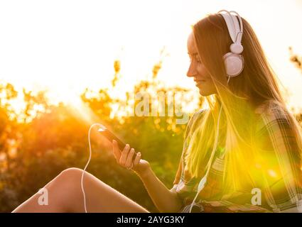 Happy young blonde woman with long hair and blue eyes listening to music with white headpones sitting outside at sunset. Stock Photo