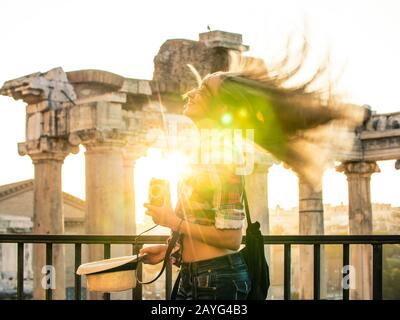 Beautiful young woman shaking long blond hair at Roman Forum at sunrise. Happy smiling tourist with vintage camera. Lens flair. Rome, Italy Stock Photo