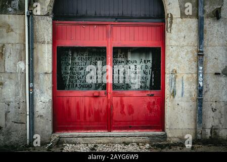 Colorful bright red wooden door in arched doorway - Stock Photo
