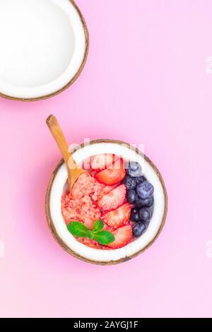 Top view of coconut bowl with healthy berry smoothie on pink background - Stock Photo