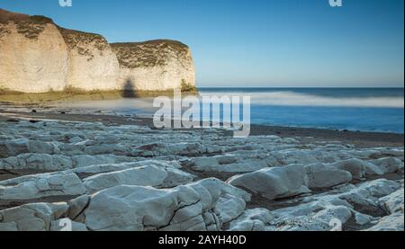 The Flamborough cliffs at North Landing in East Yorkshire, with a stony beach in the foreground - Stock Photo