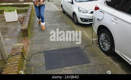 charging cable for an e-car lying on the sidewalk, a mat preventing to stumble, Netherlands