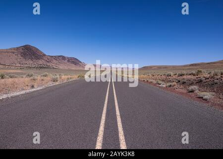 Straight asphalt road running between hills into the horizon. A road in a high desert of South Oregon - Stock Photo
