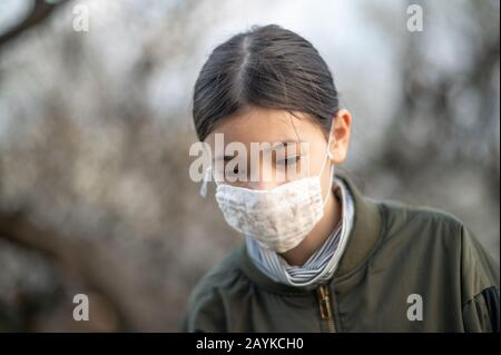 Young girl /child of mixed Asian -European ethnicity wearing a face mask to avoid virus / allergy. Close up outdoor shot. - Stock Photo