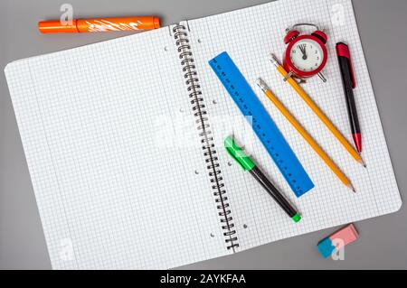 Pencils, a pen and a ruler lie on an open notebook. An alarm clock reminds of time. Office. School supplies. - Stock Photo