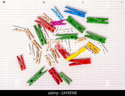 Wooden clothespins of different colors and different sizes lie on a sheet of notepad. Bright colors. - Stock Photo