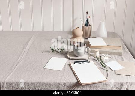 Artistic wokspace, still life scene. Paint brushes, pencils in ceramic holder, vase, cup of coffee, olive branches and blank paper card mockups on lin - Stock Photo