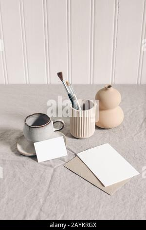 Artistic wokspace, still life. Paint brushes, pencils in ceramic holder, vase, cup of coffee and blank paper card mockups on linen tablecloth. Art sup - Stock Photo