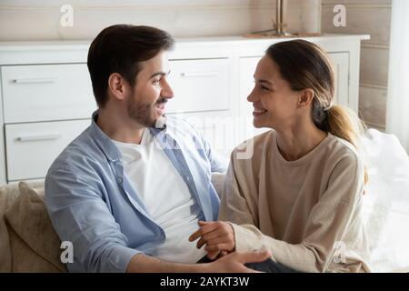 Happy young couple relax on couch talking at home - Stock Photo