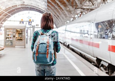 A young tourist girl with backpack waits for train on railway station - Stock Photo