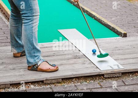 People playing mini adventure golf on a beautiful sunny summer day - Stock Photo