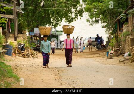 Myanmar women carrying big bamboo basket on their head, walking along the sandy road by the beach in Myanmar - Stock Photo
