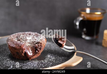 Homemade chocolate lava cake on a black plate with a coffee on a black background - Stock Photo