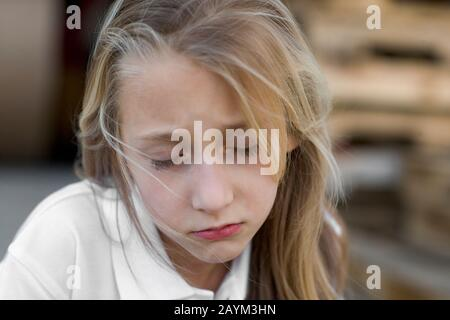 A sad girl with blond hair, looking down. - Stock Photo