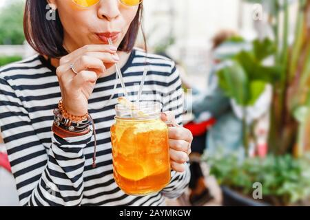 Happy female hipster student drinks a cool lemonade through a straw in a summer outdoor cafe - Stock Photo