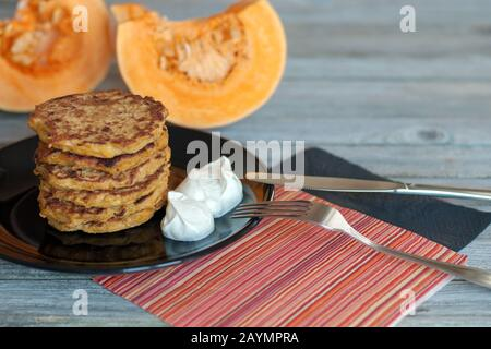 Pumpkin pancakes stack on black plate, yougurt on the side, fork, knife, black and red napkins on wooden table, squash slices on background - Stock Photo