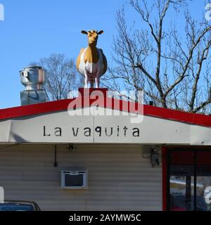 A life size cow sits atop La Vaquita Taqueria in Durham North Carolina. - Stock Photo