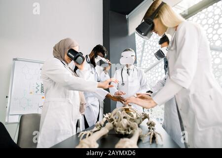 Team of multiethnic professional doctors, surgeons, orthopedists, students wearing VR goggles working with human skeleton model in modern classroom - Stock Photo