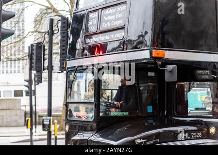 The Ghostbustour old London Routemaster bus painted black. Ghost Bus Tours retired London bus used for spooky transport around city. Dismembered arm - Stock Photo
