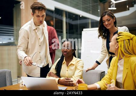 young man in white T-shirt giving a helping hand to new co-African worker who is sitting at the table in front of the laptop.help , advice