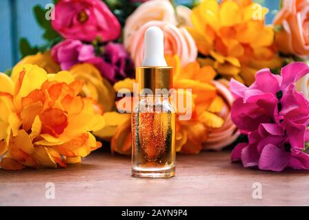 Cosmetic serum in a fashionable bottle with a pipette. Against the background of flowers. - Stock Photo