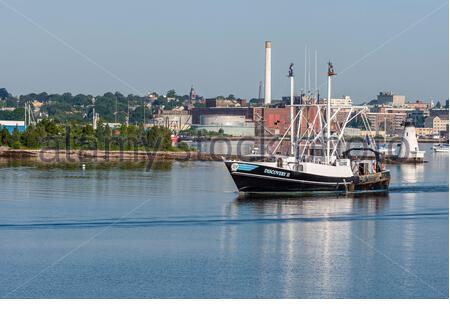 New Bedford, Massachusetts, USA - July 26, 2019: Scalloper Discovery II, hailing port New York, NY, outbound from New Bedford on windless summer morni - Stock Photo