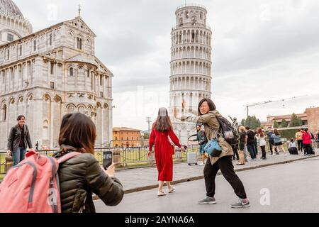 16 OCTOBER 2018, PISA, ITALY: Crowds of tourists making funny poses in front of the famous leaning tower in Pisa - Stock Photo