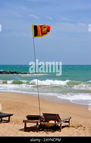 Sri Lanka, Tangalle beach, sri lankan flag and sunbeds - Stock Photo