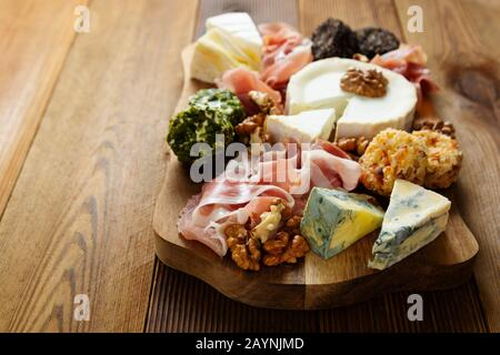 Cheese plate, various types of cheeses, grapes, walnuts and honey and prosciutto. Wooden cutting board. - Stock Photo