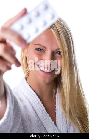 Frau mit Pillenpackung im Mund - Stock Photo
