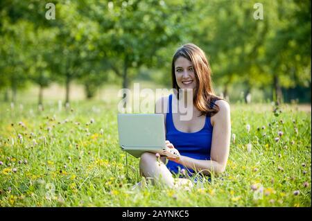 Junge Frau arbeitet mit Laptop - Stock Photo