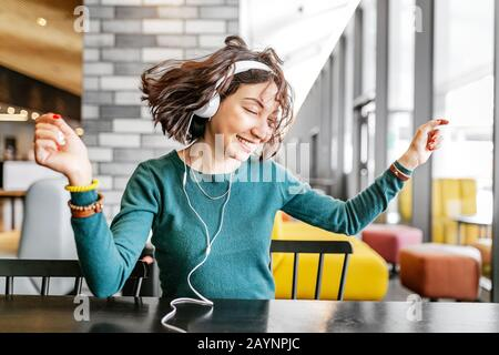 Young happy woman wearing headphones listening to her favorite song by wi-fi internet - Stock Photo
