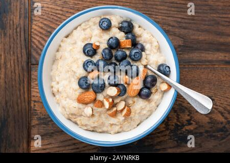 Oatmeal porridge bowl with blueberries and chopped almonds on rustic wooden table, top view. Healthy breakfast food - Stock Photo