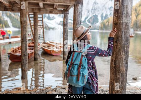 Asian girl traveler at the majestic Braies lake in South Tyrol, Italy. Vacation and adventure outdoors in nature park concept - Stock Photo