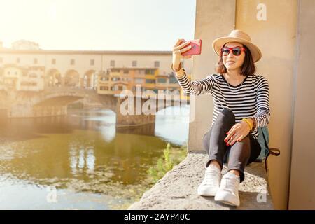Happy asian young traveler girl taking selfie near Ponte Vecchio Bridge