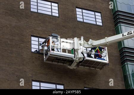 A portrait of two window washers, using a crane to get to the top windows of the building in a big box to do their cleaning job in comfort. - Stock Photo