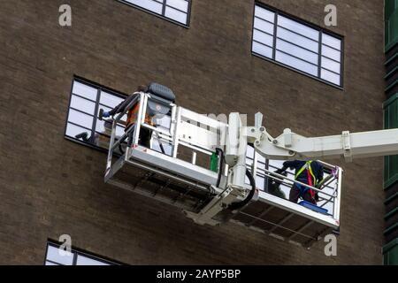 A close up portrait of two window washers, using a crane to get to the top windows of the building in a big box to do their cleaning job in comfort. - Stock Photo