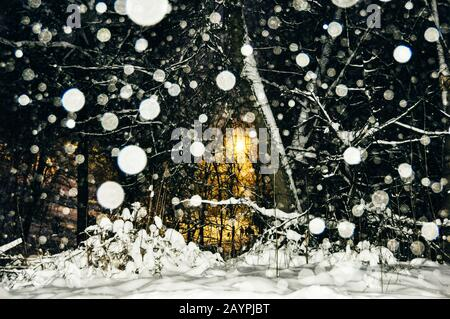 snow flakes at night. yellow lantern in the dark - Stock Photo