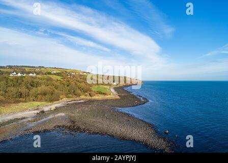 Atlantic coast at the entrance to the Belfast Laugh in County Antrim, Northern Ireland. Far view of Blackhead Lighthouse on a steep cliff. Aerial view