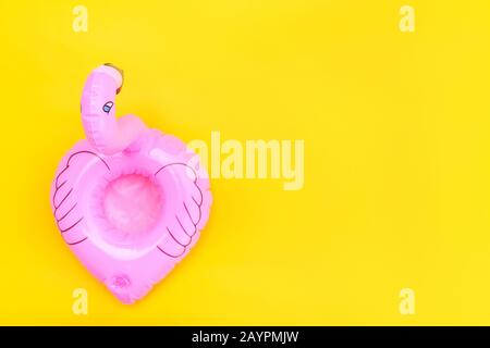 Summer beach composition. Simply minimal design with pink Inflatable flamingo isolated on yellow background. Pool float party, trendy celebrity fashion concept. Flat lay top view copy space - Stock Photo