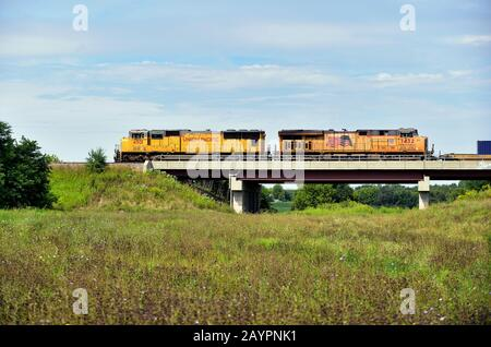LaFox, Illinois, USA. A Union Pacific freight train, lead by two locomotive units, passes over a bridge. - Stock Photo