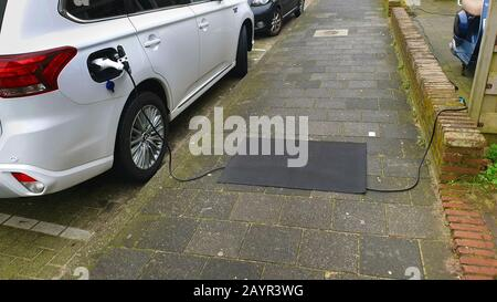 charging cable for an e-car lying on the sidewalk, a mat preventing to stumble, Netherlands - Stock Photo