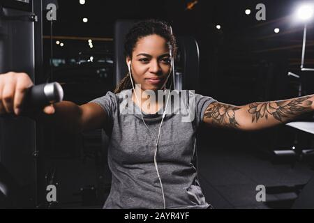 selective focus of happy and tattooed african american woman listening music in gym - Stock Photo