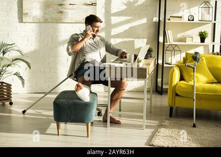Handsome freelancer with broken leg on ottoman talking on smartphone and using laptop at table - Stock Photo