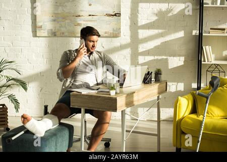 Handsome freelancer with broken leg using laptop and talking on smartphone at table in living room - Stock Photo