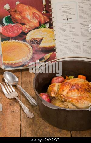 Dutch-style roasted chicken with baked red potatoes, carrots and celery, in a cast iron pot on a rustic wood table, with an old cookbook in the backgr - Stock Photo