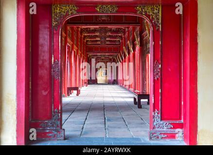 Symmetrical Corridor and Red Doors in the Forbidden Purple City, Historic Imperial Palace and United Nations World Heritage Site in Hue, Vietnam - Stock Photo